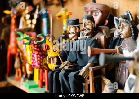 Wooden figurines of St Simon and other characters for sale in a market in Antigua Guatemala. Famous for its well - Stock Photo