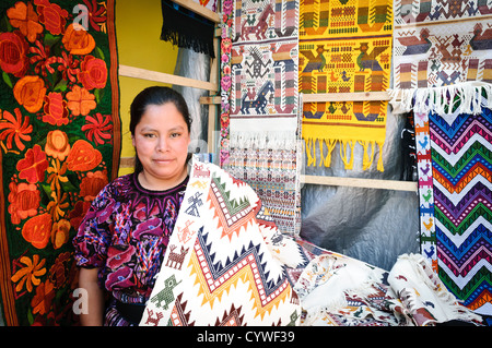 A local woman posing with her woven textiles at the Chichi market. Chichicastenango is an indigenous Maya town in - Stock Photo