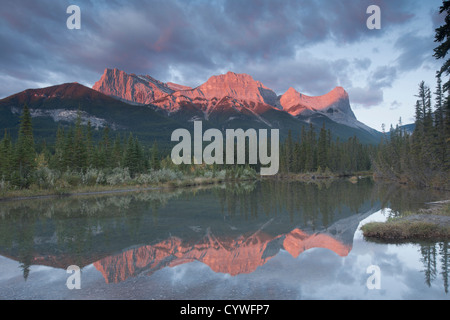 Mount Lawrence Grassi and Ha-Ling Peak in Canmore at sunrise. Reflected in a pool of water from the Bow River. - Stock Photo