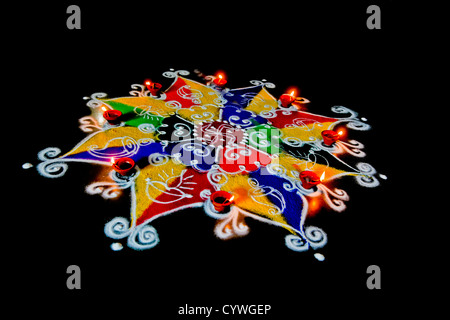 Divali rangoli and divas a colorful pattern on black background - Stock Photo