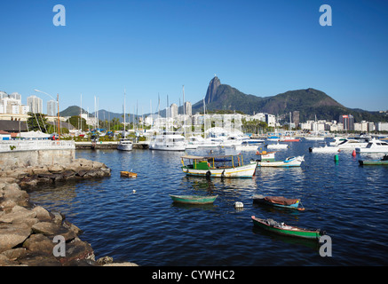 Moored boats in harbour with Christ the Redeemer statue in background, Urca, Rio de Janiero, Brazil - Stock Photo