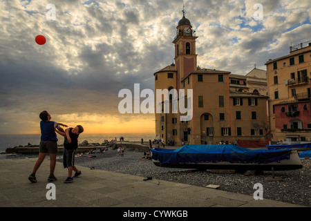Boys playing basketball at Camogli, Riviera di Levante, Liguria  with the church Santa Maria Assunta in the background - Stock Photo