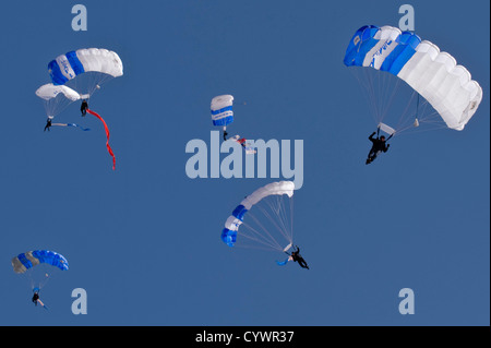 The U.S. Air Force Academy's Wings of Blue Parachute Team steer their parachutes for precision landings during Aviation - Stock Photo