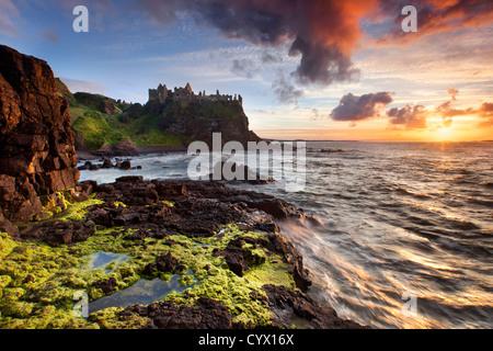Duluce castle at sunset on the Antrim coast, Northern Ireland. - Stock Photo