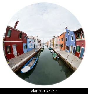180-degree circular fisheye view down a canal in Burano, with still water, moored boats and brightly-painted houses - Stock Photo