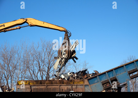 Grappling Crane dropping metal objects into shredder at Metal Recycling Plant E USA - Stock Photo