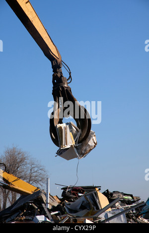 Grappling Crane lifting metal objects for shredder at Metal Recycling Plant E USA - Stock Photo