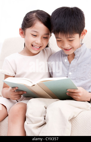 Little boy and girl reading a book - Stock Photo