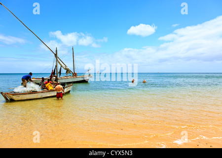 A tourist watches as fishermen ready their nets for a days fishing on Inhaca Island Mozambique - Stock Photo