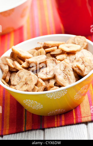 dried banana chips in bowl - Stock Photo