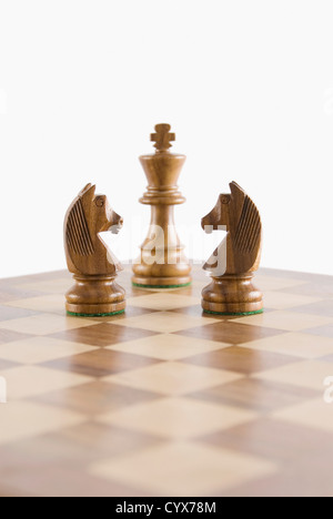 Close-up of chess knights face to face with a chess king on a chessboard - Stock Photo
