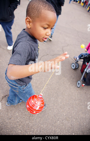 african american boy tween spinning a top balloon string twirl play game games fun interest child kid guy - Stock Photo