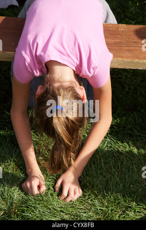 blond girl child kid leaning over bench showing only back side torso hands in grass blonde exhausted weary sad - Stock Photo