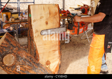 MAN MALE CARVING CLOSEUP wood carving with chain saw CHAINSAW CARVERS artists carvers chain-saw lumberjack - Stock Photo