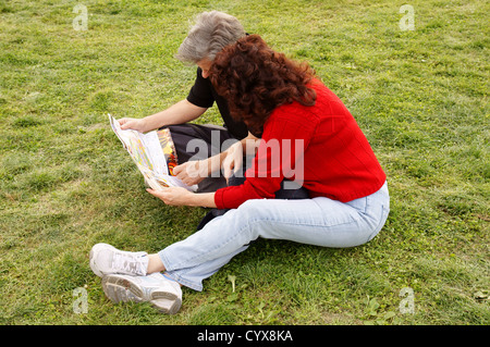 couple senior citizen aged sitting on grass reading map candid man male woman female adult grownup mature - Stock Photo