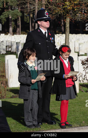 Sunday 11th November 2012 Brookwood Military Cemetery Pirbright UK. A Surrey Police Officer and children with service - Stock Photo
