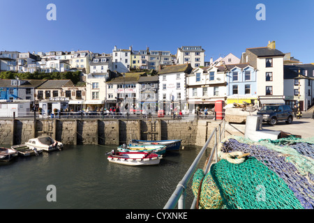 The two sides of Brixham in Devon, UK. Fishing nets lie on the quayside, next to small fishing boats and pleasure - Stock Photo
