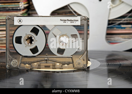 Compact-cassette being on a vinyl record and audio analog tape and vinyl record covers in the distance - Stock Photo