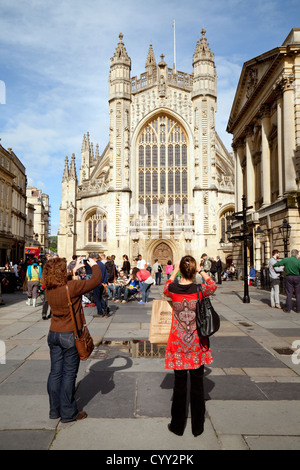 Tourists taking a photo of the Abbey, the city centre, Abbey Churchyard, Bath, Somerset UK - Stock Photo