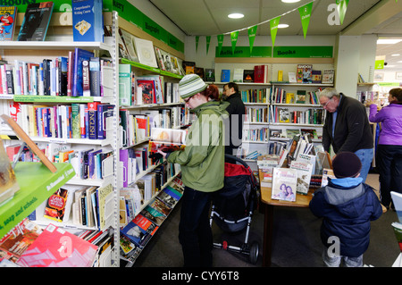 People browsing books in an Oxfam charity shop in England - Stock Photo