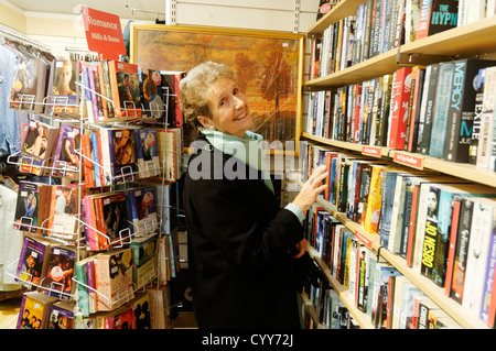 An older woman browsing books in a charity shop in England - Stock Photo