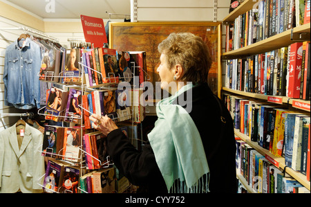An older lady looking at Mills and Boon books in a charity shop in England - Stock Photo