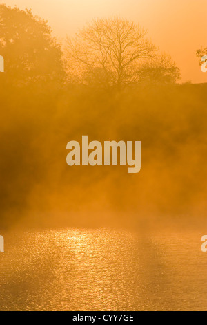 Early Morning Mist and Sunrise Over Cropston Reservoir - Stock Photo