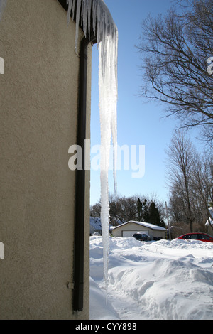 Icicles hanging from the eaves of a house. - Stock Photo