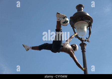 acrobatic performance artist at an old street lamp on the hill of Sacre Coeur in Paris - Stock Photo