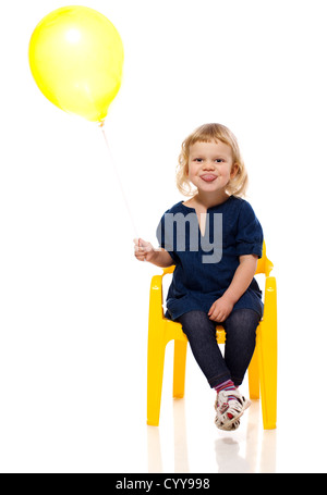 Funny Girl holding balloon making faces isolated - Stock Photo