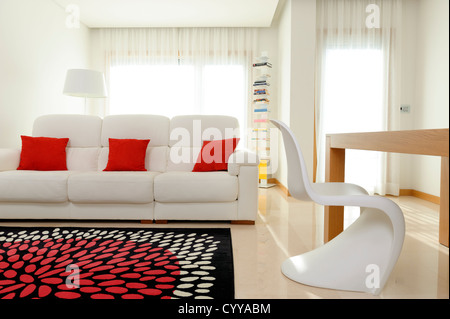Living room with white sofa, dining table and Vitra Verner Panton chair - Stock Photo