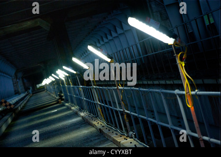 A service road illuminated by site lighting, trackside in the Britannia railway bridge, Wales - Stock Photo