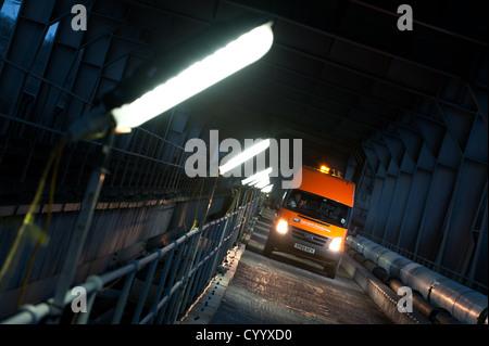 A van illuminated by site lighting, trackside in the Britannia railway bridge, Wales - Stock Photo