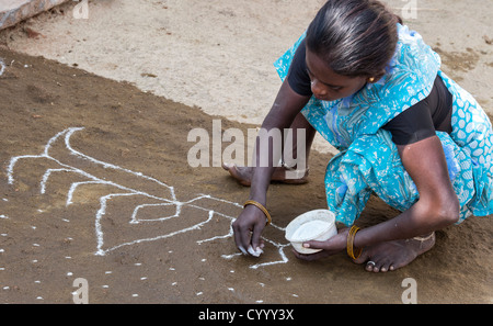 India woman making a Rangoli festival design outside her rural indian village home. Andhra Pradesh, India - Stock Photo