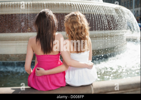Back view of two young female friends with arms around sitting by water fountain - Stock Photo
