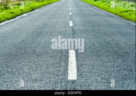 Amn empty straight road with white lines leading to a vanishing point on the horizon in the Fens UK - Stock Photo