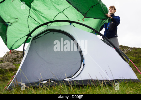 A woman wafting a fly sheet over a tent on grassy ground. - Stock Photo