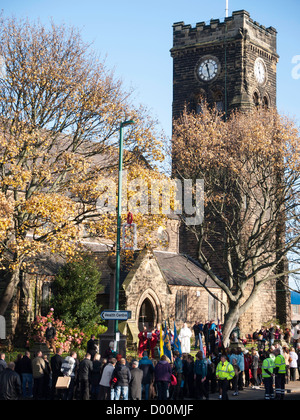 Crowd at a village church and adjacent war memorial on Remembrance Sunday - Stock Photo