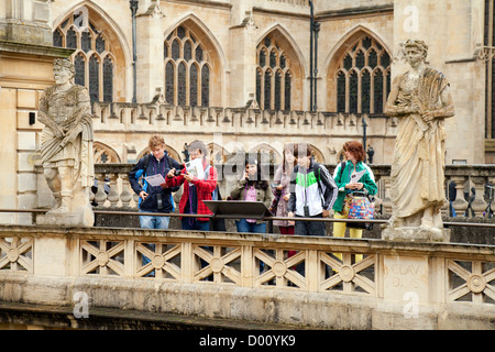 Teenage tourists at the abbey and Roman Baths in Bath Spa, Somerset, UNESCO World Heritage site, UK - Stock Photo