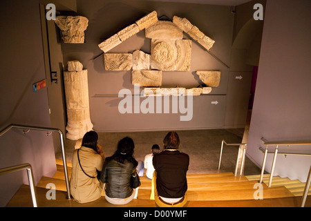 Tourists looking at the head of the gorgon in the museum, the Roman Baths, Bath cSpa, Somerset UK - Stock Photo
