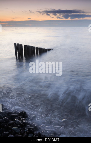 Incoming tide washing over rocks and wooden groynes on Bossington Beach, Somerset, UK. - Stock Photo