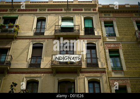 Indignats protest banner hanging from apartment building balcony in Barcelona, Spain. - Stock Photo