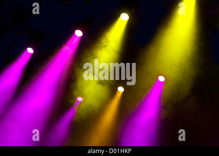 Shafts of coloured colored lighting shine through  atmospheric smoke in a dramatic way to light an empty stage - Stock Photo