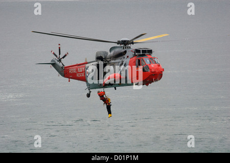 A search and rescue helicopter from RNAS Culdrose in Cornwall, England, UK, during a sea rescue exercise. - Stock Photo