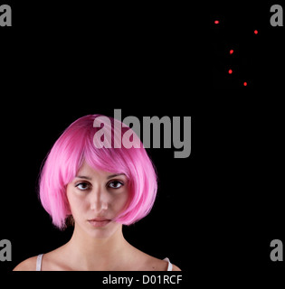 Portrait of young woman wearing pink wig against black background - Stock Photo