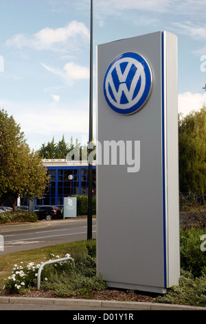 A large Volkswagen logo on display outside a VW car dealership in the UK. - Stock Photo