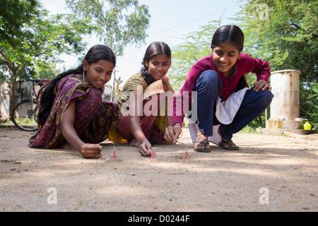 Indian teenage girls lighting firecrackers at Diwali festival. Andhra Pradesh, India - Stock Photo