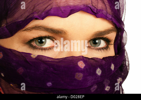 A closeup of a very beautiful Indian or asian woman wearing a purple veil - Stock Photo