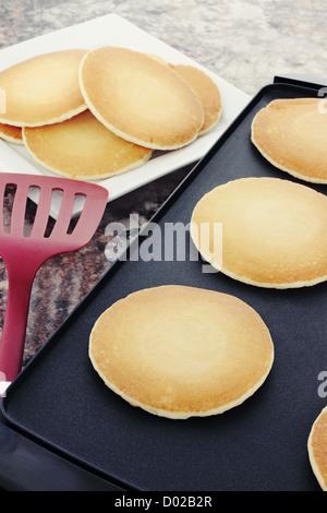 Preparing fresh pancakes on a non-stick griddle. - Stock Photo
