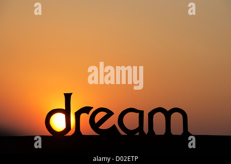silhouette dream word at sunset with sun in the d stock photo
